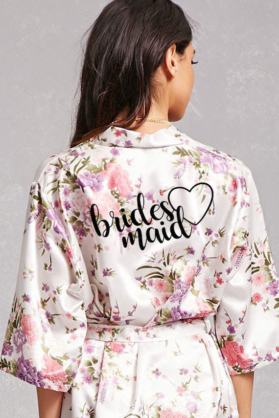 """[Image description: A girl with long, black hair stands with her back to the camera. She is wearing a floral, satin robe with the word """"Bridesmaid"""" printed on the back alongside an outline of a heart.]"""