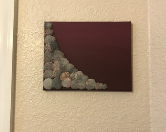 Grey shells tinged with burgundy glued to berry ombre painted canvas