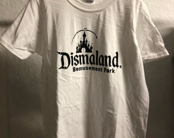 Child L (9-11 years) - White : Banksy - Dismaland T-Shirt (1077)