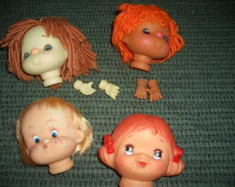 four vintage doll heads two with hands