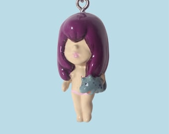 Girl with creature mobile phone charm