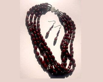 Cranberry Twist: Garnets, sterling silver, German silver, South Sea seeds. Necklace and two pairs of earrings set.