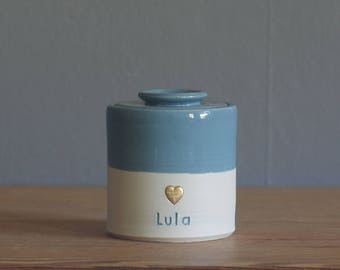 custom urn. ceramic lid, straight shaped urn with custom stamp. modern simple urn for ashes. blue and gold urn shown.