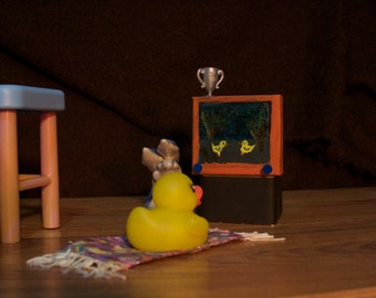 Photograph of a rubber duck watching TV.