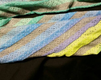 A soft infinity scarf with stripes of gray, yellow,  purple, blue and teal