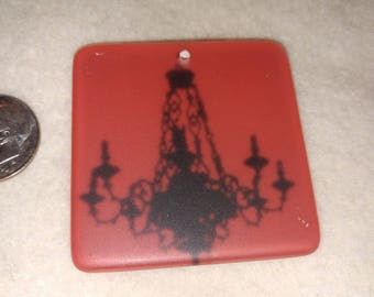 red frosted lucite 1.75 inch square pendant with image of black chandelier on it