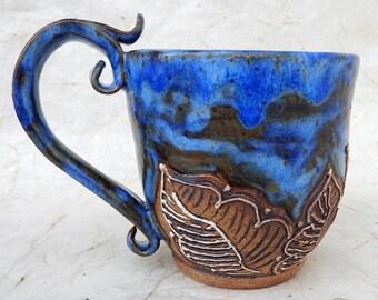Stoneware mug with carving and slip decoration