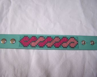 Cuff embroidered in shades of old pink, fuchsia and green