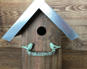 Outdoor rustic birdhouse with mint green bird perch and metal roof