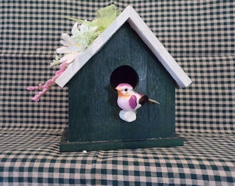 Wooden birdhouse with flowers on its roof and birdie perched in front