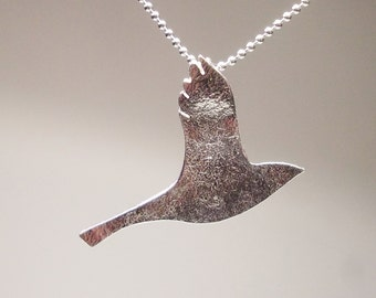 A silver crow flies pendant