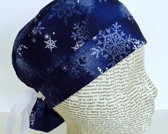Ponytail Scrub Cap scrub hat featuring a dark blue material with white and silver snowflakes with a winter theme and a white ribbon