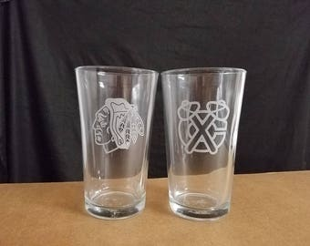 A set of 2 laser etched pint glasses, Chicago Blackhawks, 2 different logos ,Face and Hatchet logos