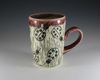 Wheel-thrown, red glazed hand-carved mug with ladybug design