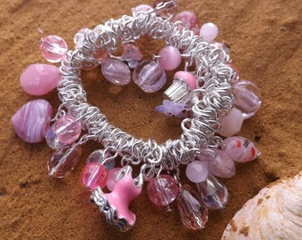 Pretty pink charm bracelet with lots of glass beads on a silver-plated elastic bracelet
