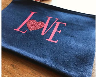 A zip bag or purse with love design and glitter heart with red tassel detail