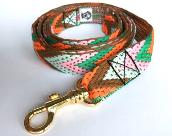 Dog leash: woven herring bone pattern in orange, pink, green, blue and brown. Golden brass carabiner