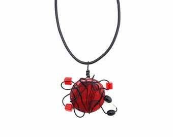 Red and black necklace that can be worn as a pendant on a strip of leather or at the neck on a hoop
