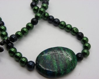necklace made of black and green glass with 1 large turquoise bead