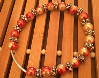 7.5 inch silver and orange and yellow beaded stretch bracelet.