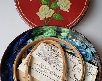 Vintage red tin with white roses filled with embroidery floss hoops and instructions