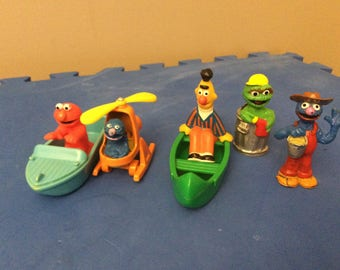 Five figurines from the Muppets Sesame Street Elmo including boat