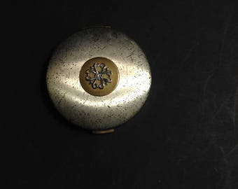 Avon two-tone compact, lid is silver tone with gold tone circle and silver tone filigree flower.