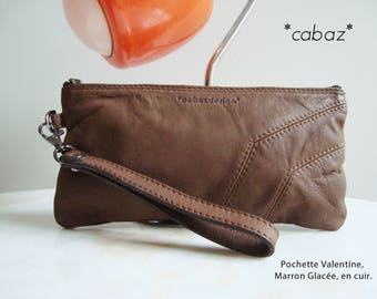 Brown color leather clutch.
