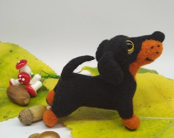 A dog, a soft toy, a toy made of wool, a furred toy, a dachshund, a felt dog, a merry dog, a black dachshund, dog lovers