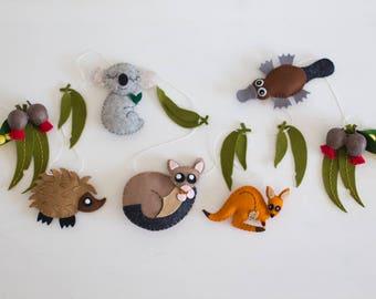 Australian animal nursery garland featuring koala, possum, kangaroo, platypus and echidna with gumleaves and Australian wildflowers.
