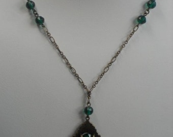 1920's Green lass Square Cut Pendant Set in an Embossed Brass Diamond Shaped Frame.