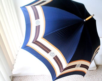 Authentic vintage 80s navy blue with a wide beige trim umbrella-parasol, surrounded with a Burberrys logo. Made by Burberry in England.