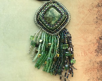 Bead embroidered minty green swirly pigment cabochon with asymmetrical shaded fringe
