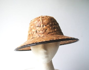 Safari vintage 60s, dark beige straw, hand woven , helmet style unisex hat with a  brown vinyl tream. Mint condition. Size 23.