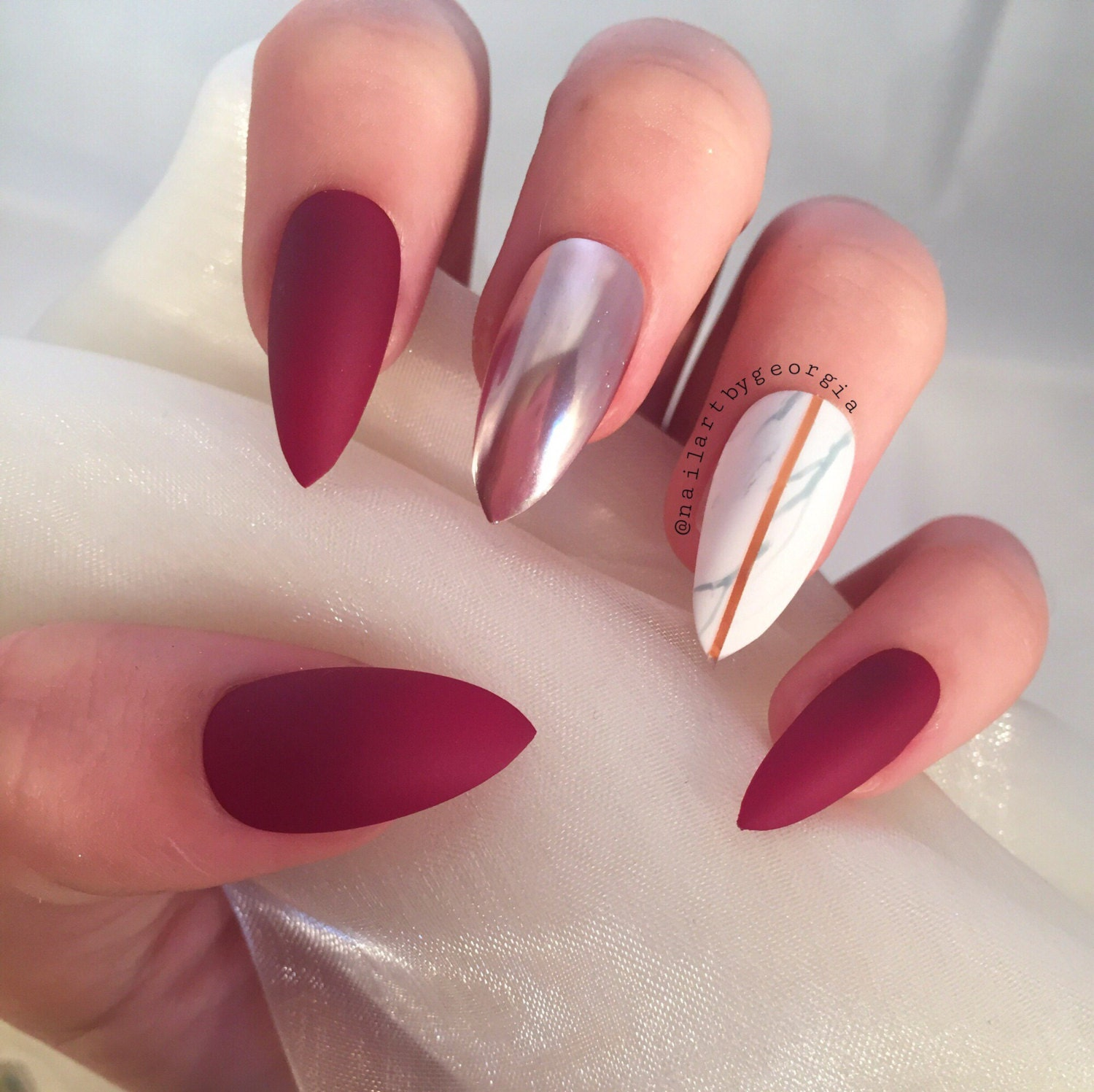 Matte berry red stilettos with marble and chrome false nails