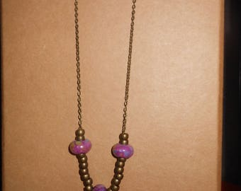 long necklace with bronze and purple ceramic beads