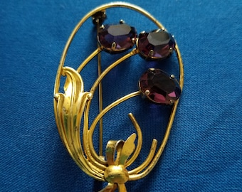 Gold toned brooch with purple colored glass stone flowers