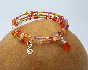 Oranges and Reds Beaded Memory Wire Bracelet with handcrafted silver charms.
