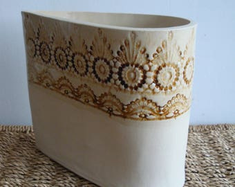 Teardrop shaped ceramic vase with lace detailing.