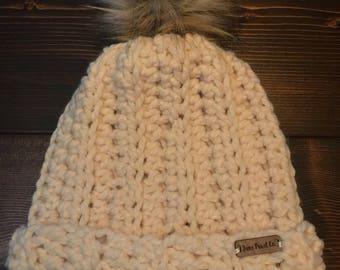 Women's crocheted winter hat with faux fur pom
