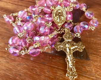 Handmade rosary in 8mm Czech Glass Fire Polished pink beads with ornate, gold immaculate medal center and ornate crucifix.