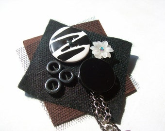 Artisan felt brooch.Kazuri button,hematite and chain with black tulle