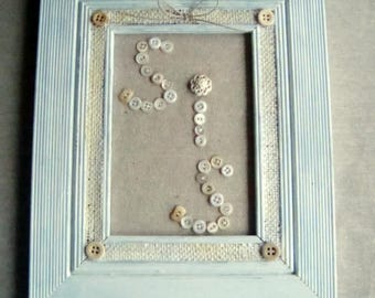 """Vintage buttons spelling word """"Sis"""" in cottage beach aqua frame."""