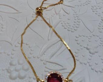 Gold slider bracelet with fuchsia center
