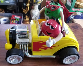 """M&M hot rod candy dispenser """"Rebel without a clue"""" featuring red and green candy"""