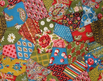 Patchwork pattered cotton fabric in greens, reds, blues and gold colors