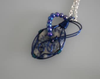 Wire wrapped pendant. Blue and white marbled cabochon wrapped with blue copper wire & blue beads.