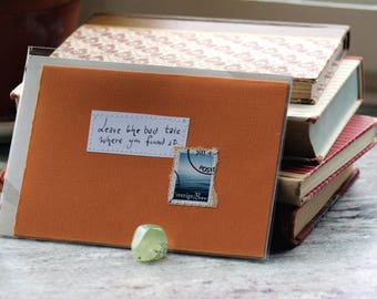 Leave the bad tale where you found it .. Dark orange card with handwritten quote and Swedish sea postal stamp