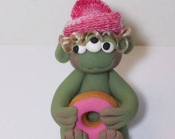 Three eyed Donut monster with blonde hair and striped pink hat. polymer clay monster