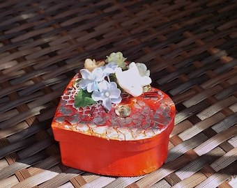 A heart shaped gift box in red with a lid, embellished with a bunch of paper flowers